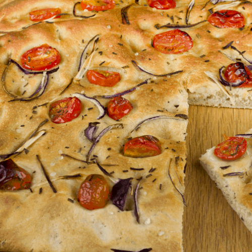 A slice from a loaf of fresh Focaccia Bread.