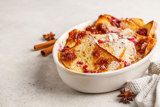 French toast casserole with raspberries, powdered sugar and cinnamon, white background, copy space.