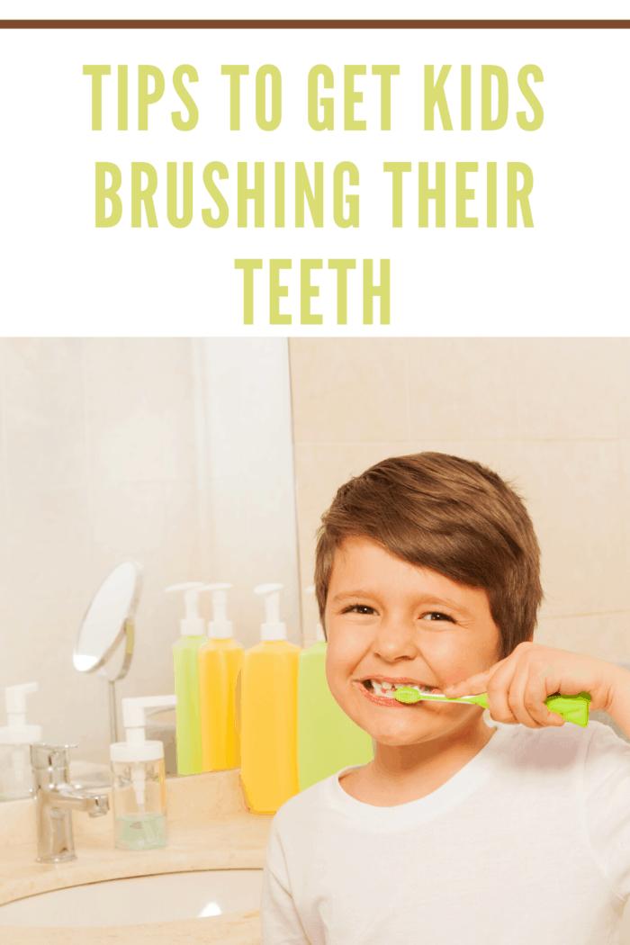 young boy smiling while brushing teeth
