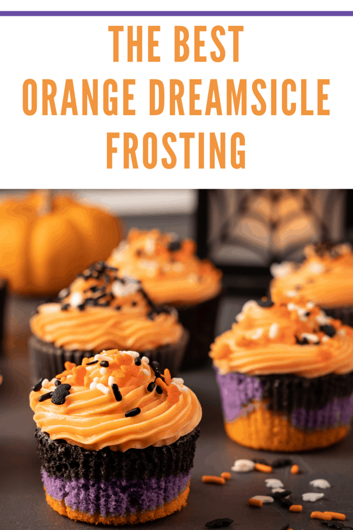 Halloween cupcakes with purple, black and orange cake bottom frosted with a swirled orange creamsicle frosting. Cupcakes are decorated with Halloween themed sprinkles, bats , ghosts and multi colored sprinkles. A pumpkin and spider web lantern can be seen in the bac