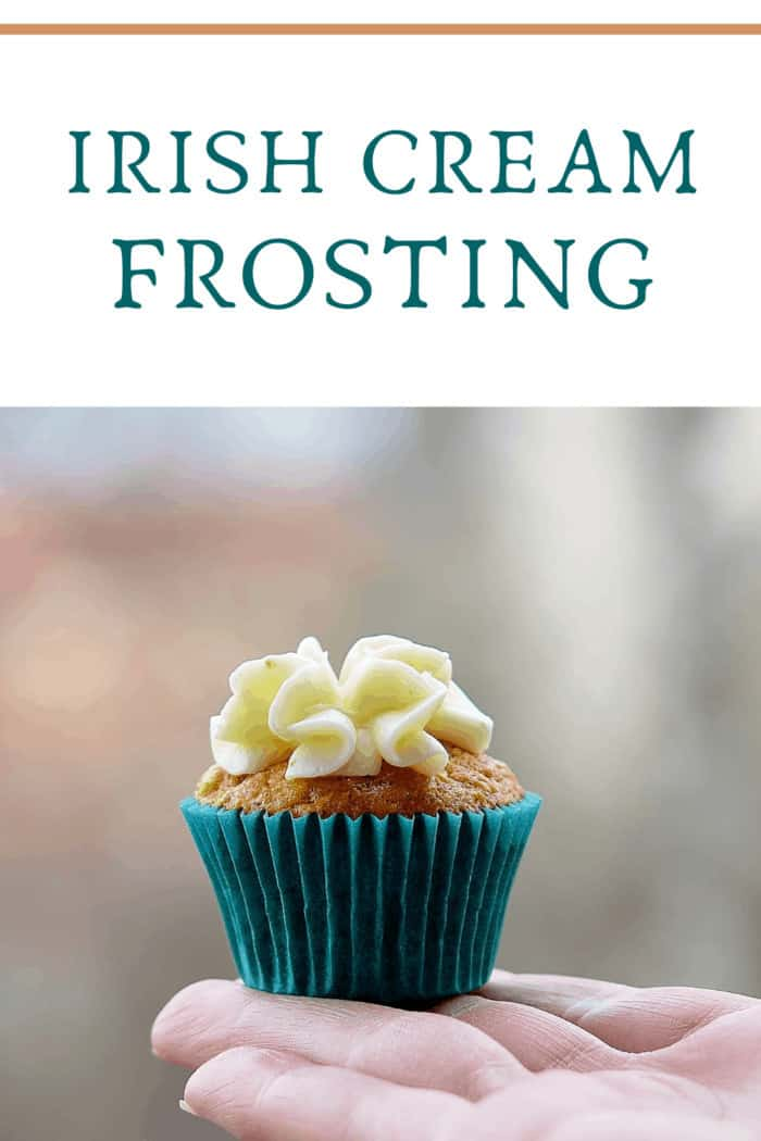 Hand Holding Cupcake Outdoors. Cupcake topped with irish cream frosting