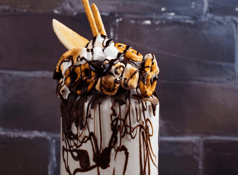 toasted marhmallow milkshake with pretzel embellisments and chocolate syrup on grunge vintage background.