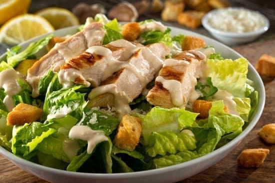 close up of chicken caesar salad in bowl