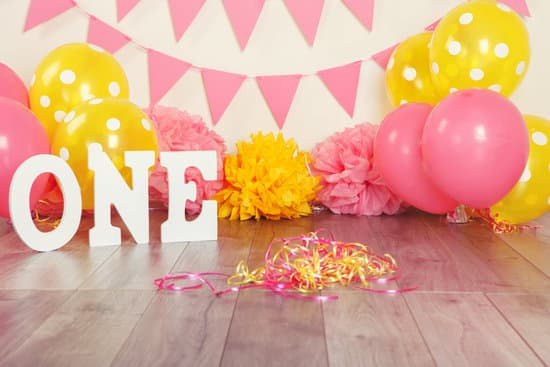 Festive background decoration for birthday celebration with letters saying one and pink red yellow balloons in studio. Cake smash first year concept.