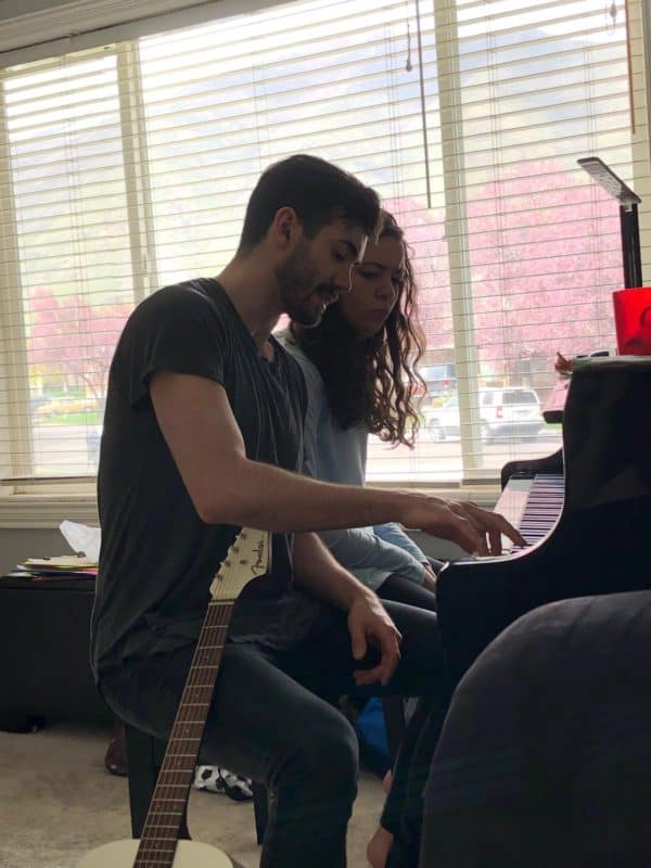 young man and young woman playing piano together