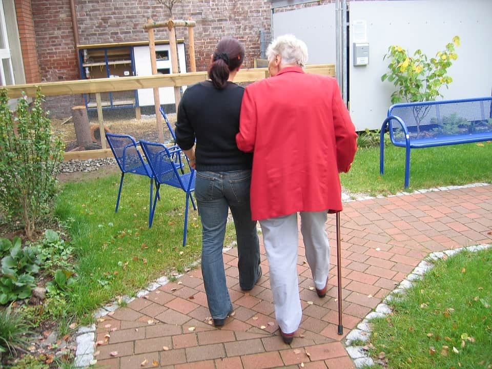 older woman walking on paved trail with young woman