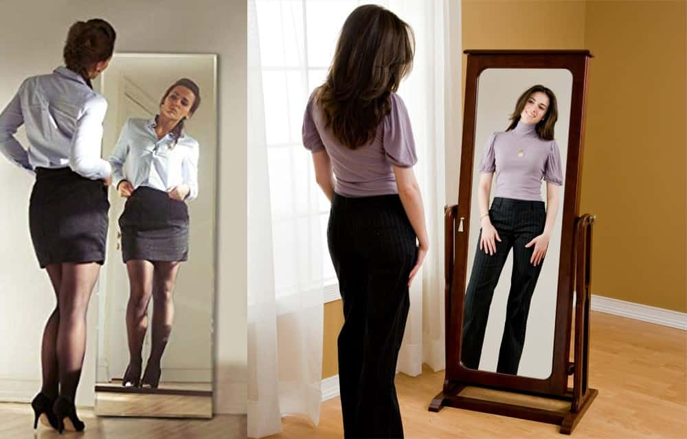 two women, one in a short black skirt with pums and the other in long black pants, both admiring themselves in a full length mirror