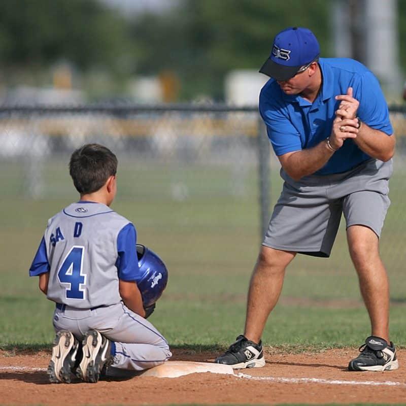 man coaching young boy about baseball