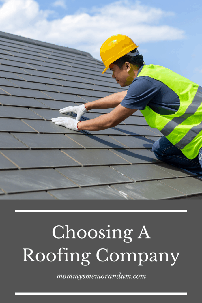 roofing contractor checking shingles on roof