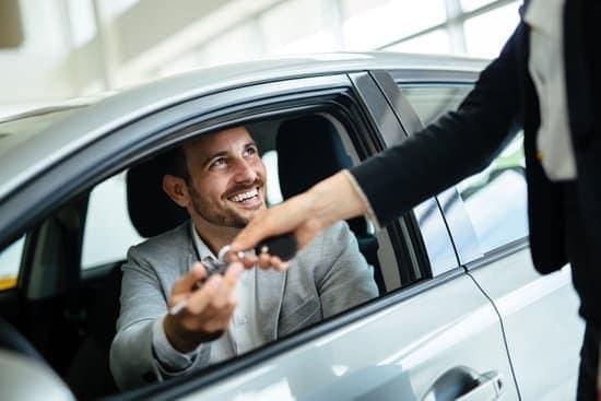man in car being handed car keys through window