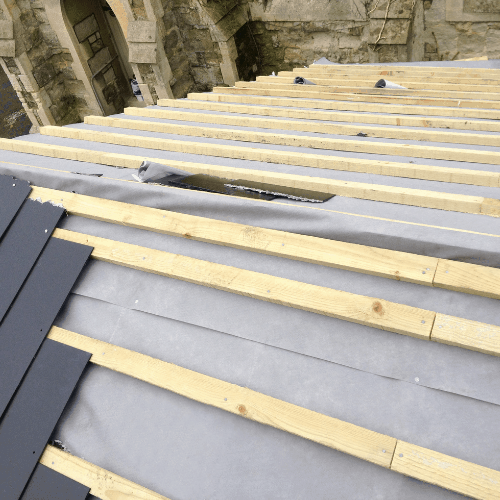 Image shows a roof being replaced with new tiles, felt and batten.