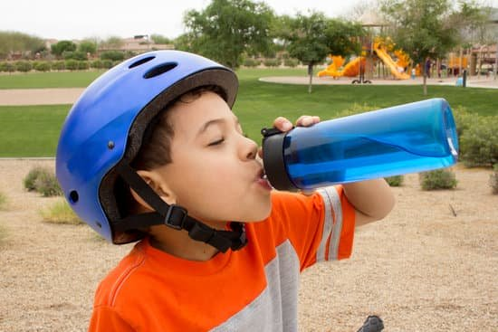 boy with bike helmet on and orange shirt drinking water from blue water bottle free of drinking water contaminants