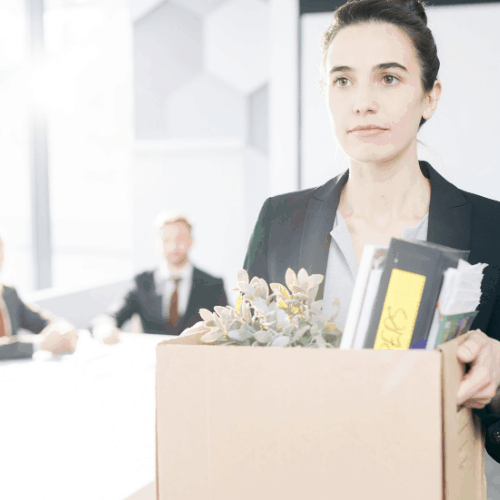 Waist up portrait of young businesswoman holding box of personal belongings leaving office after quitting job, copy space
