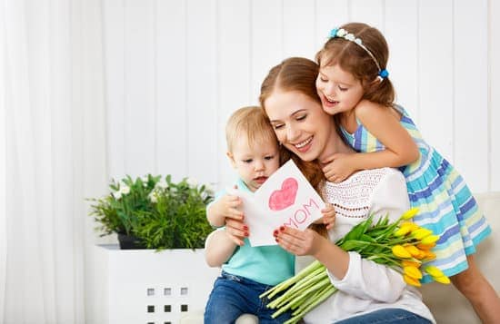 mom opening homemade mother's day card with kids