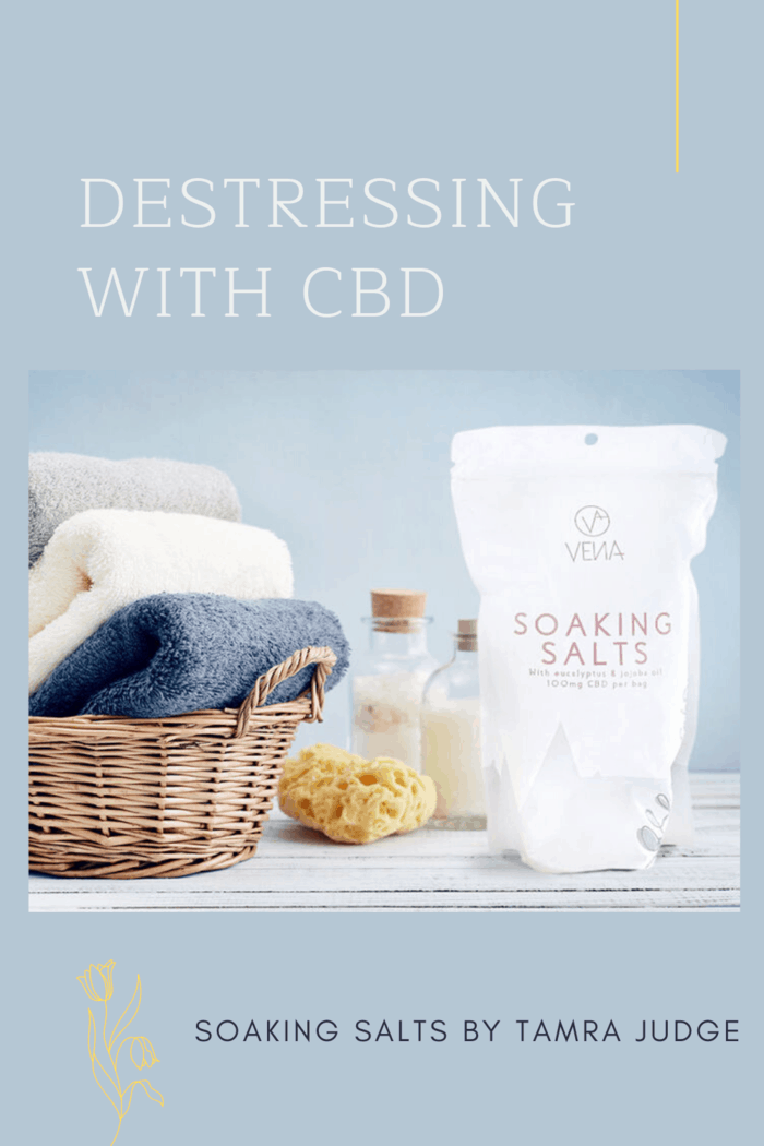 VENA CBD Soaking Salts on table next to basket of plush bath towels