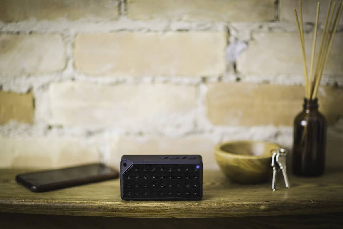 blue tooth speaker with beige brick background