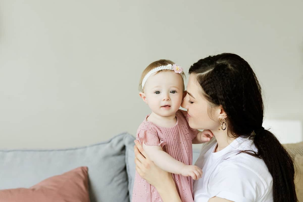 young mother cuddling toddler daughter in mauve dress with matching headband