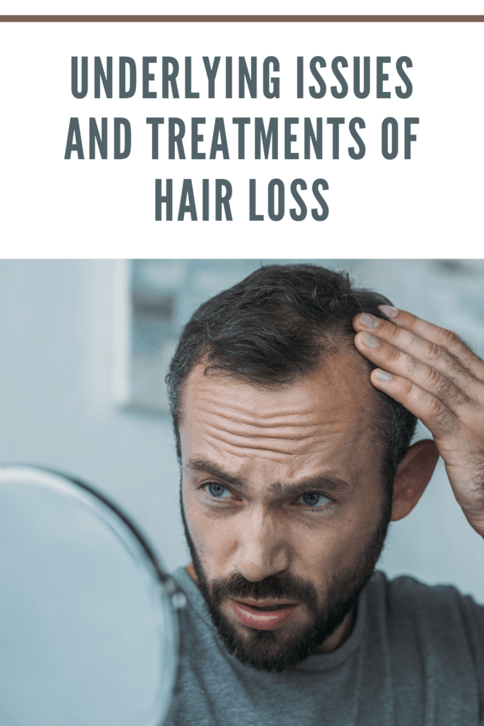 man with hair loss looking in the mirror