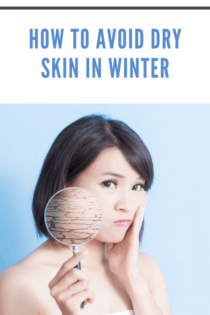 asian woman holding up magnifying glass showing dry skin in winter