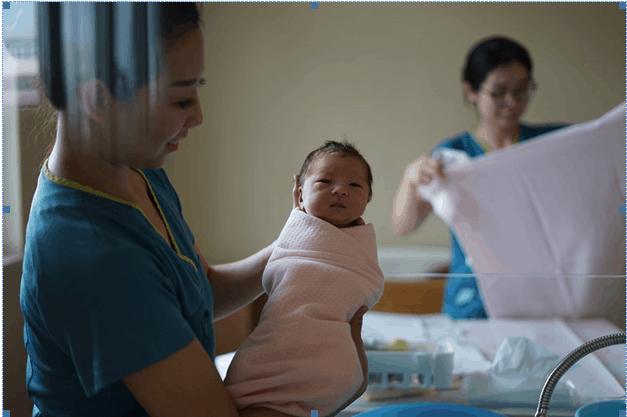 new baby bundled in pink blanket being held up by nurse