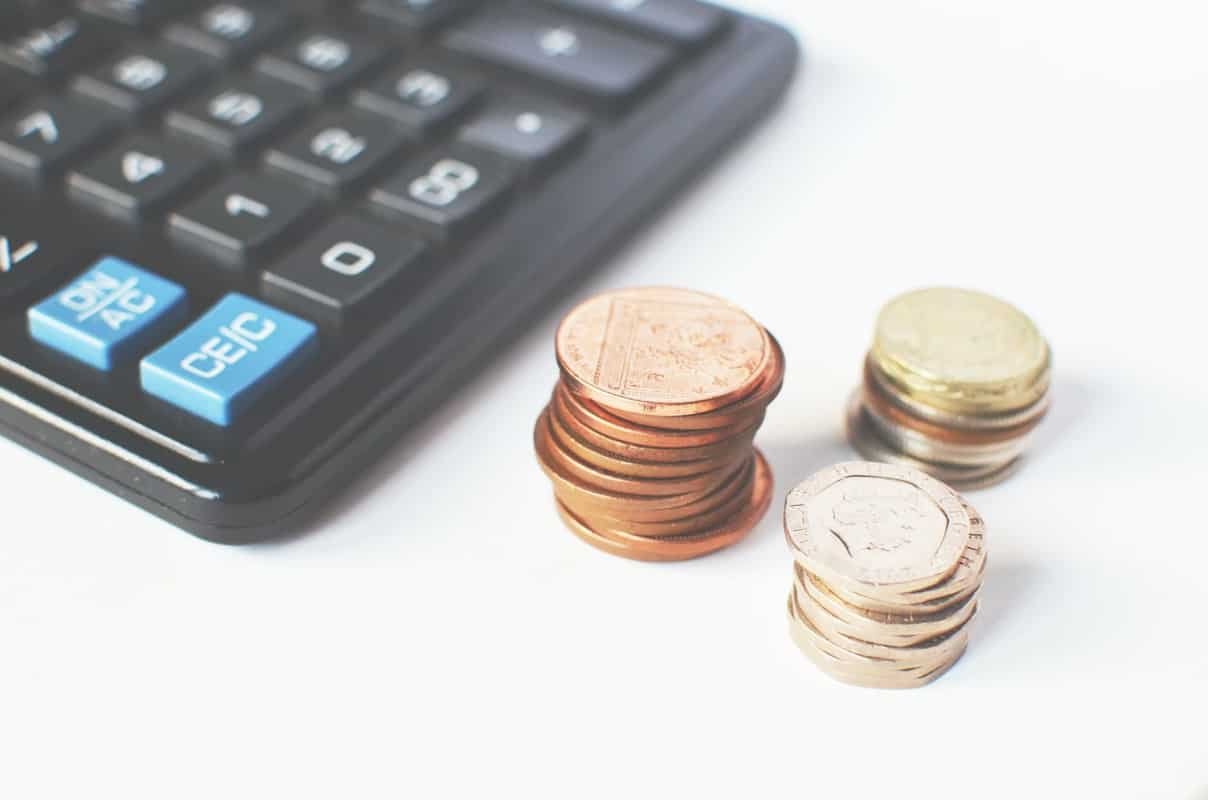 stacks of coins next to black calculator
