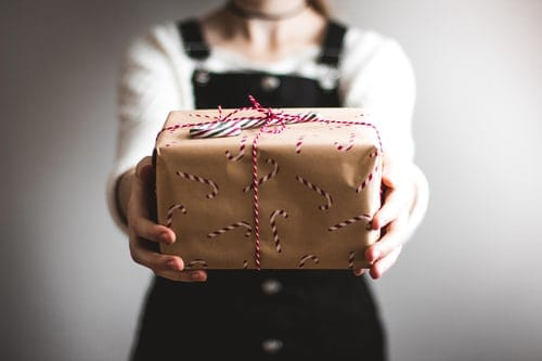 woman extending arms with package of brown paper with candy canes drawn on and tied with a red and white cord.