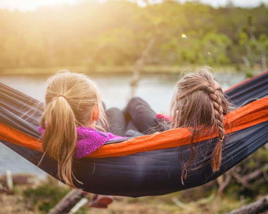 children in a hammock overlooking lake
