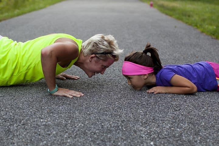mom and daughter doing push ups on road