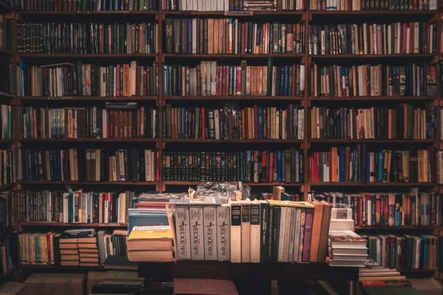 bookshelves filled with books overflowing to organized table of books