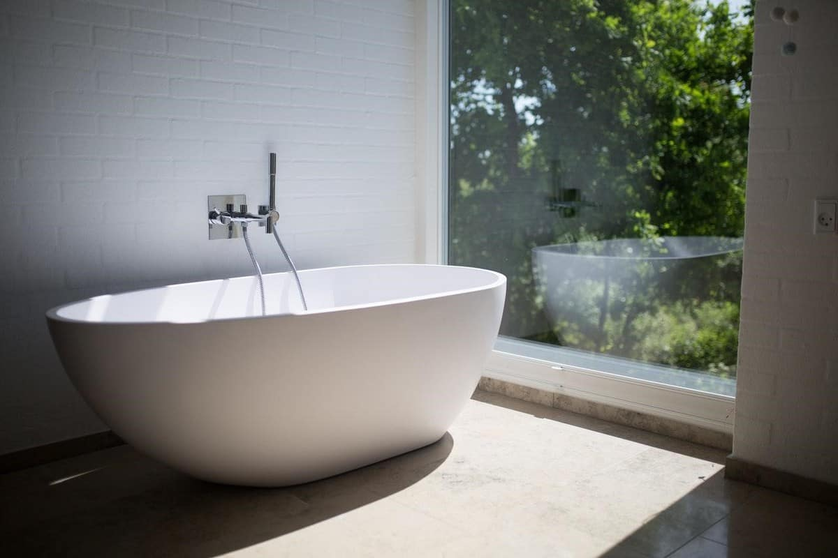stand alone bathtub next to floor to ceiling window with view of foilage