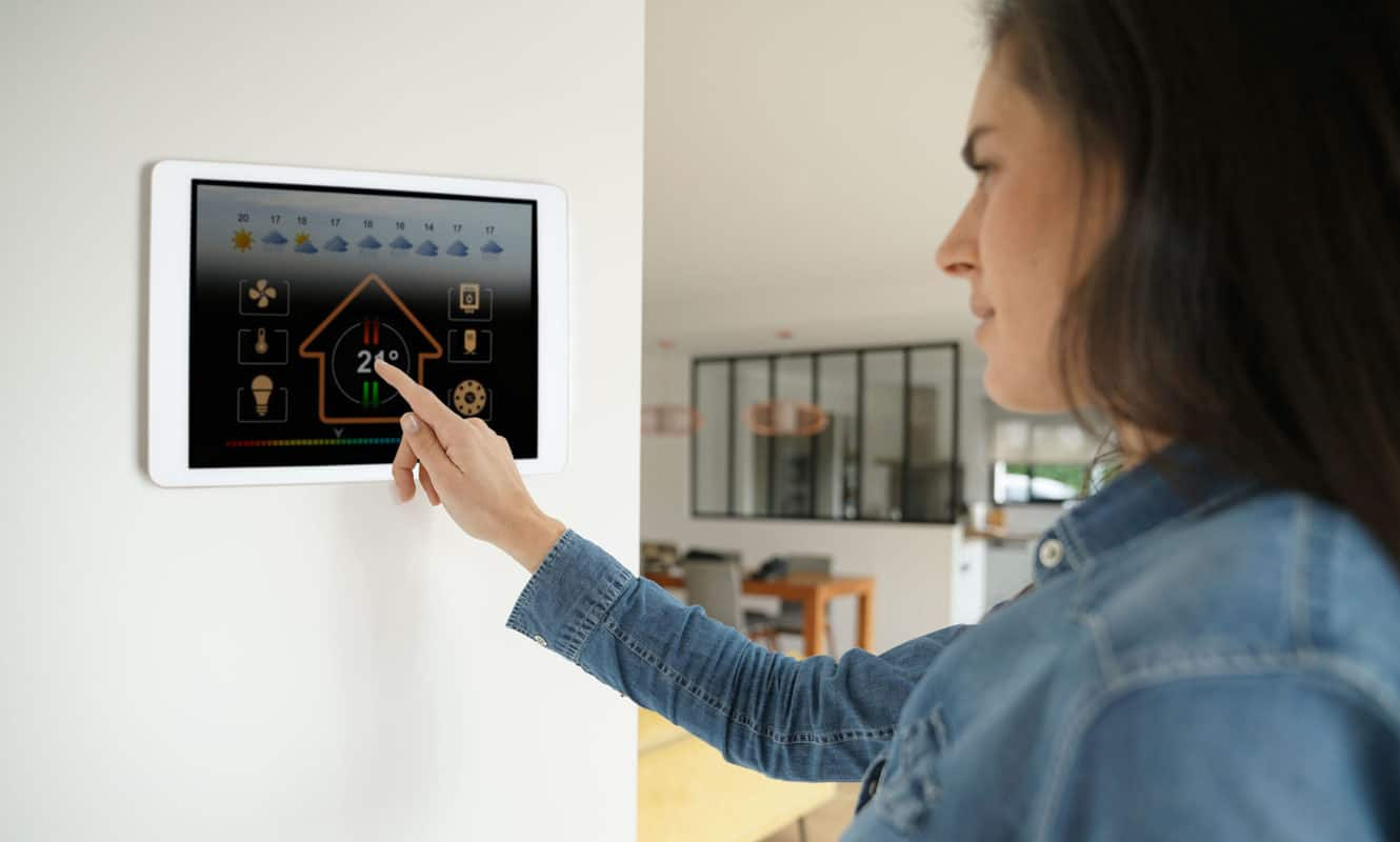woman setting temperature on smart home device