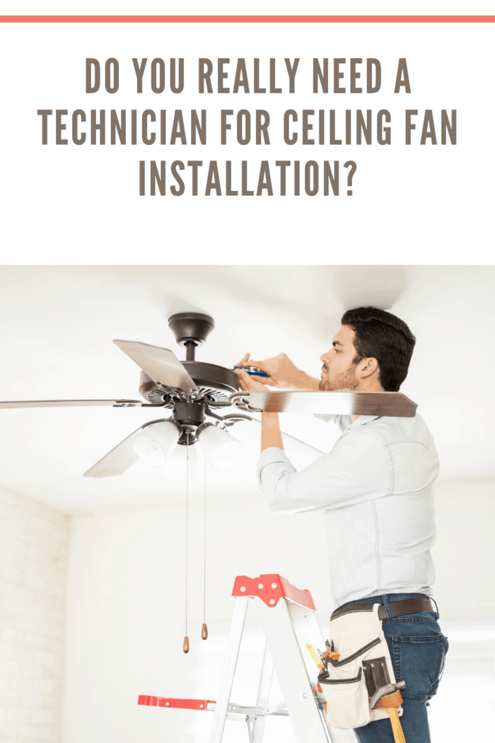 Attractive young technician stepping on a ladder and installing a ceiling fan