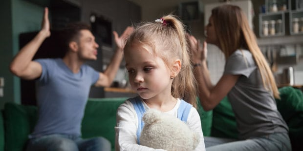 Frustrated little girl upset tired of parents fight looking away from camera, portrait of sad preschool kid daughter suffers from family mom and dad arguments or lack of attention, child and divorce concept