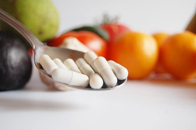tomatoes in background with supplements on a spoon represendnig if food supplements can boost the immune system.