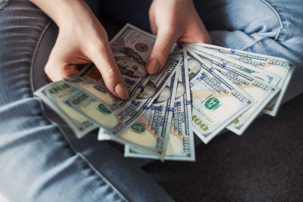 person-holding-100-us-dollar-banknotes