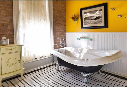 A modern contemporary classic bathroom design, furnished with a classic painted cabinet, sepia toned picture on the wall, exposed brick wall and a window, a claw foot bath tub and black and white tile pattern on the floor. Photographed in horizontal forma
