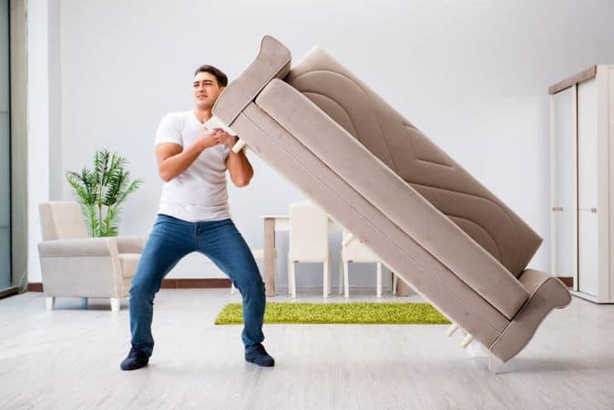 Young man moving furniture at home before learning how to prepare furniture for moving