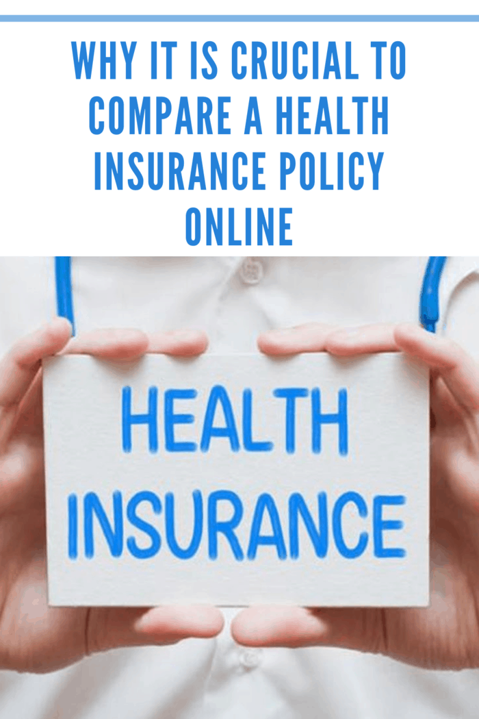 """person in white medical jacket holding small sign that reads """"Health Insurance"""" in blue."""