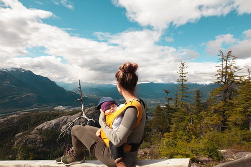 woman looking at scenic view while babywearing