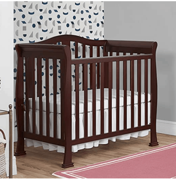 brown crib with storage in nursery with pink rug