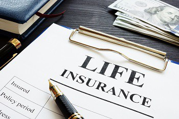 Whole life insurance pen and dollar banknotes.
