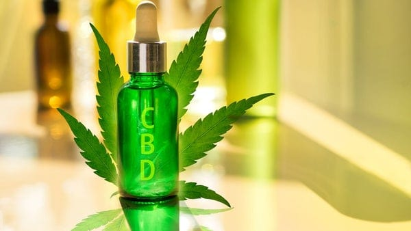 Glass bottle CBD OIL, tincture awith label on background of the laboratory cannabis oil