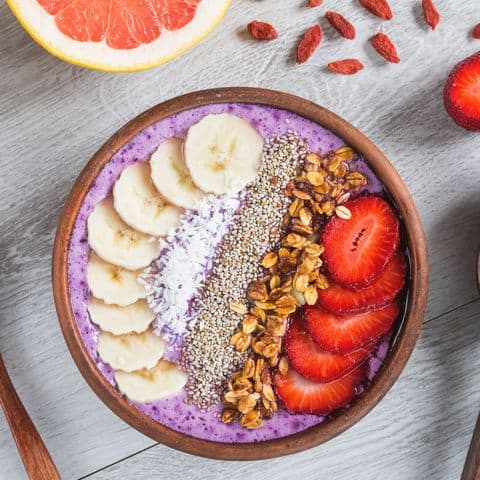 Acai smoothie bowl with superfoods. Smoothy bowl topped with banana, chia seed, coconut, strawberry and granola representing superfoods taking your skincare and beauty game to the next level