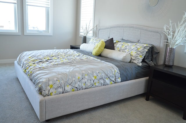 best mattress under gray bedspread with yellow accents