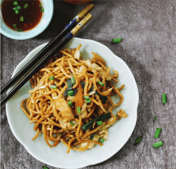 Homemade Chinese Lo Mein served with green tea overhead view