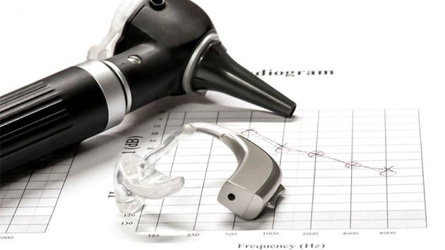 Otoscope and behind the ear hearing aid being displayed on an audiogram
