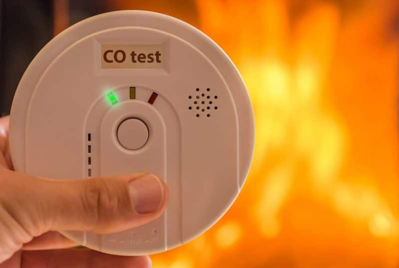 carbon monoxide poisoning alarm with fire in background
