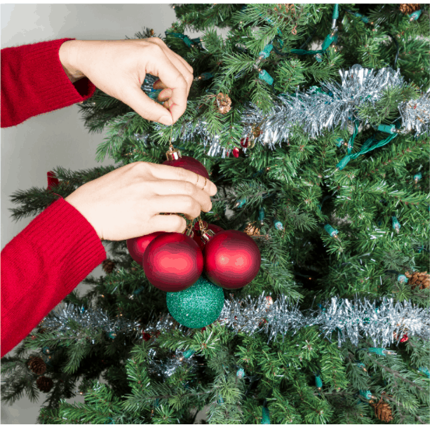 Female hands gathering red and green ornaments to be put into storage with Christmas tree in background