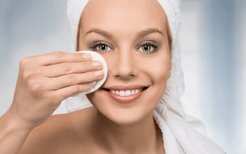 Close up of happy woman removing make- up