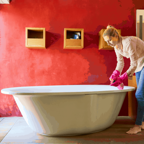 Cleaner or cleaning lady cleans a bathtub during the spring cleaning